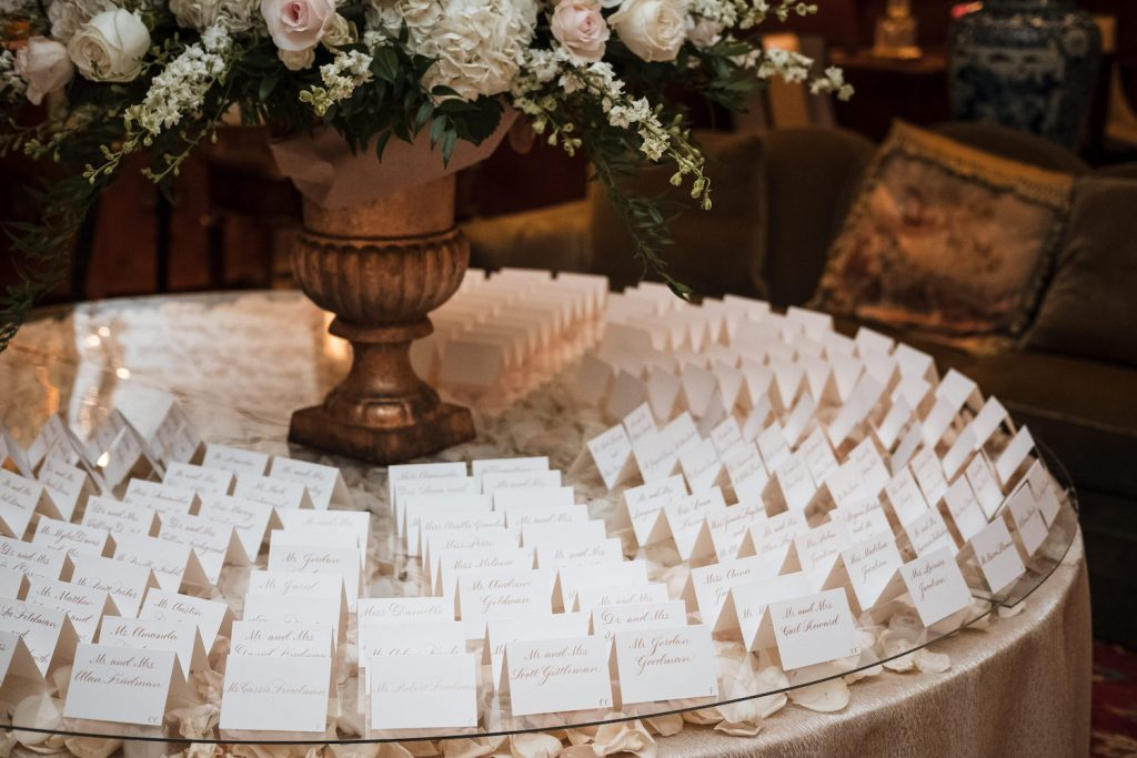 Leah E Moss - escort cards on round table with flowers
