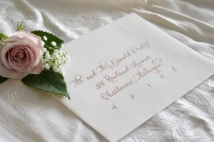 rose gold calligraphy on wedding invitation envelope