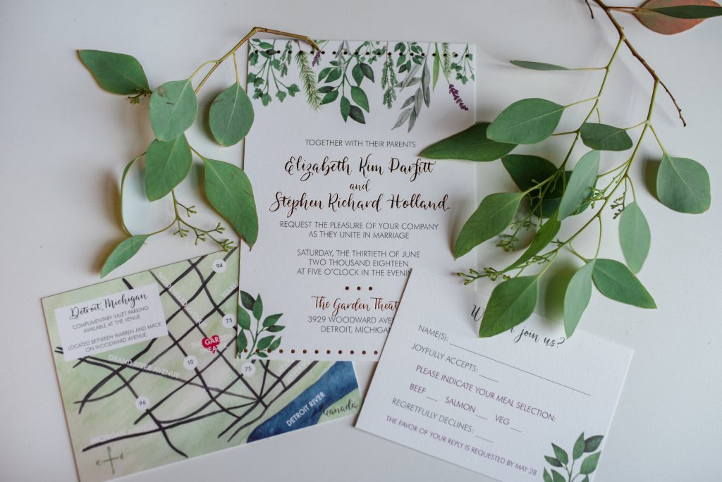 wedding invitation with greenery flat lay