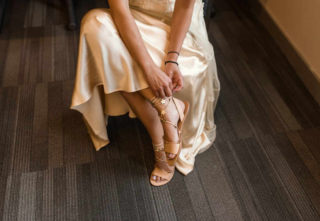 bride in ivory dress adjusting her shoes