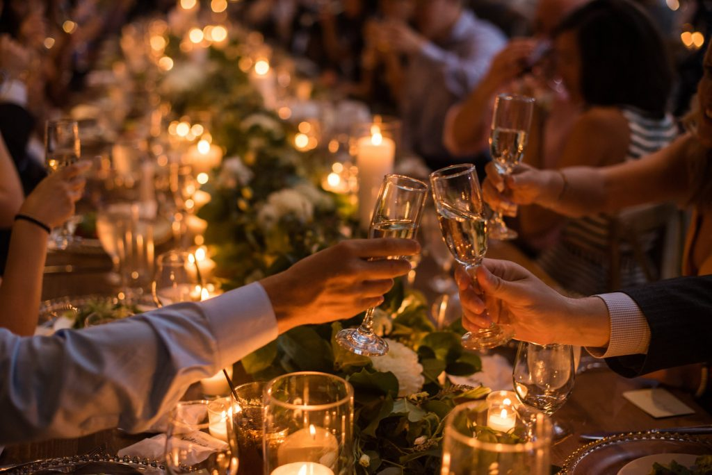 toast with champagne glasses by candlelight