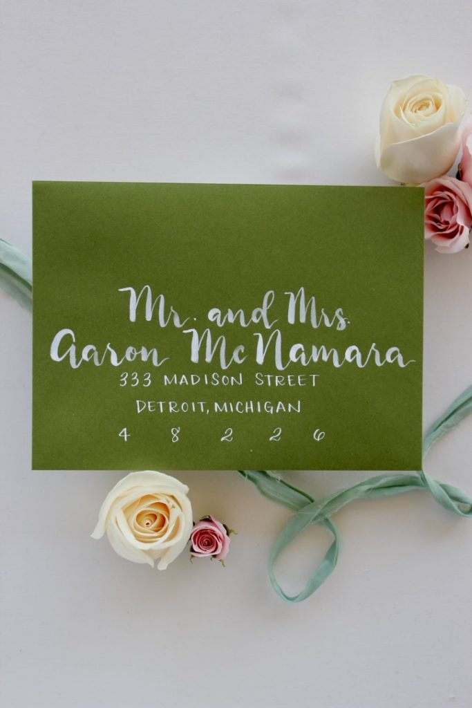 Green envelope with white brush lettering in modern calligraphy style - Leah E. Moss Designs