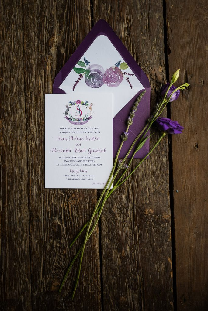 Purple wedding crest with dog, cat, and florals on purple wedding invitation - Leah E. Moss Designs