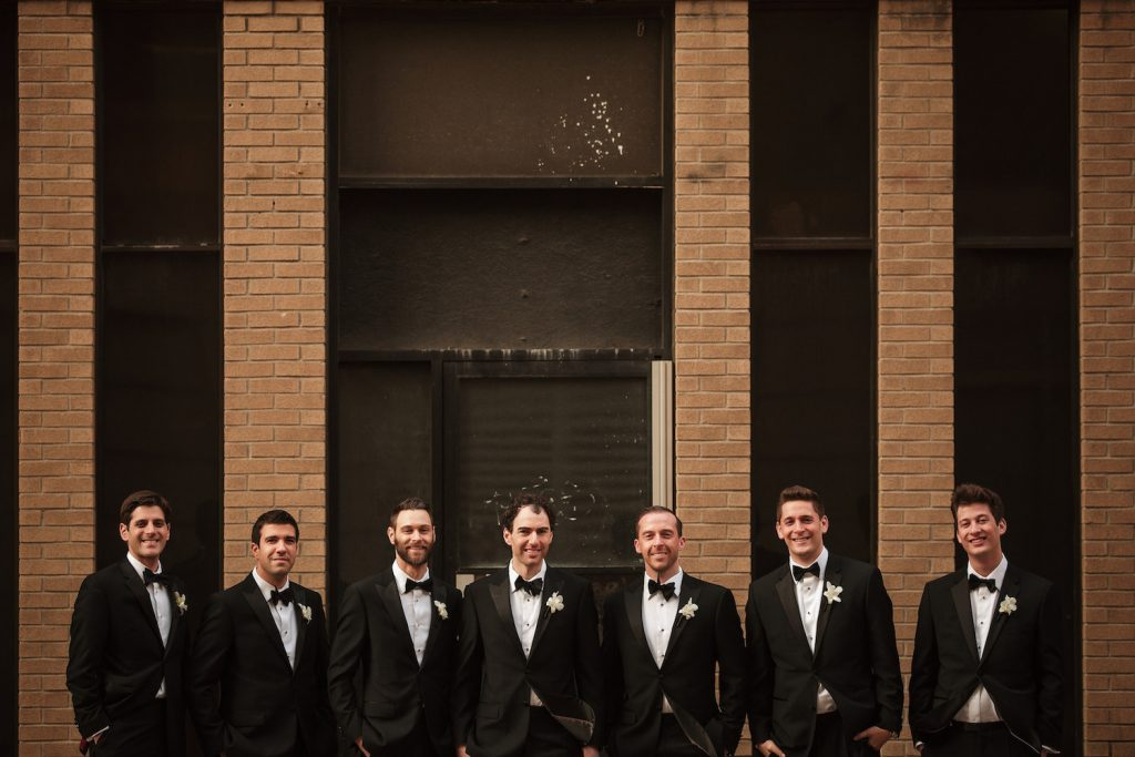 Groomsmen in black tuxedos - An Elegant Book Cadillac Wedding in black, gold, pink, and white - Leah E. Moss Designs