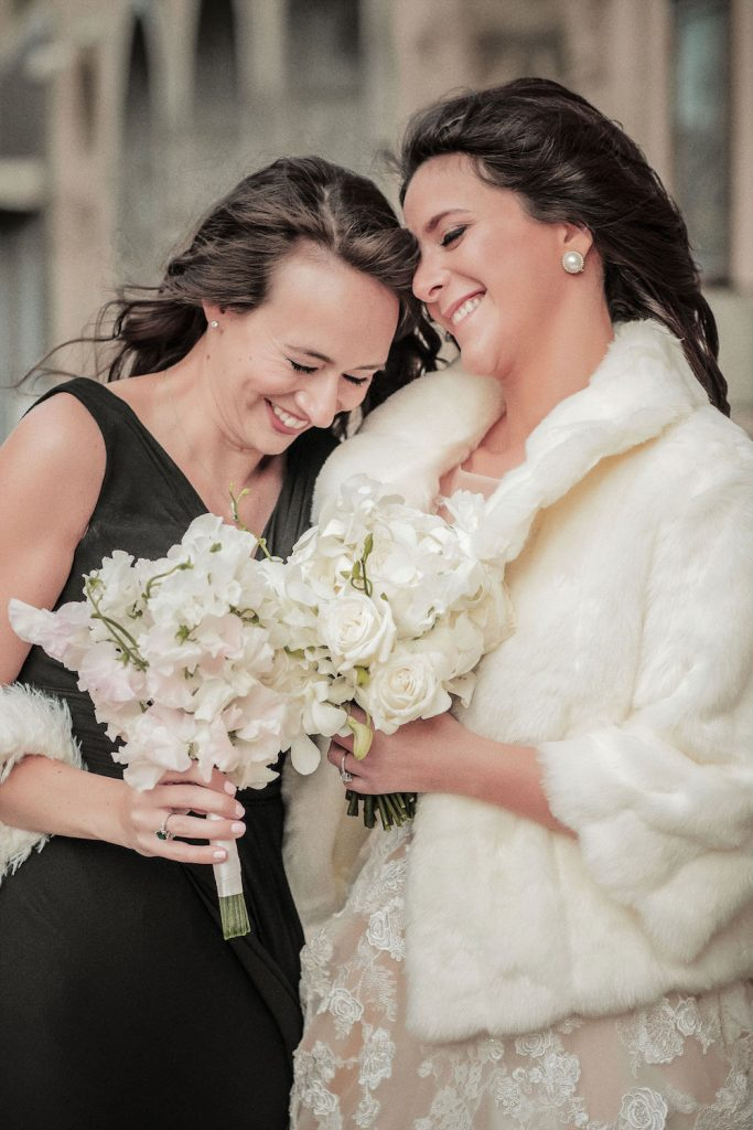 Bride in fur with maid of honor - An Elegant Book Cadillac Wedding in black, gold, pink, and white - Leah E. Moss Designs