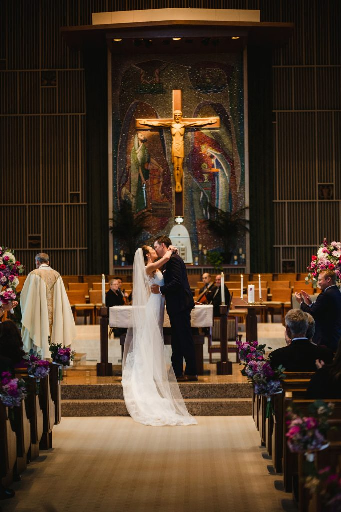First kiss as husband and wife - Purple and pink florals for wedding at Oakland Hills Country Club in Bloomfield Hills, Michigan - Leah E. Moss Designs
