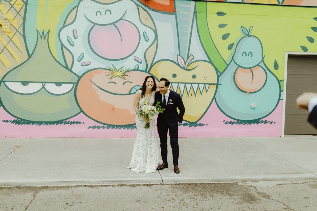 Bride and groom in front of mural - Eastern Market wedding recap from Detroit calligrapher Leah E. Moss Designs with photos by Jill DeVries Photography #detroitwedding #moderncalligraphy #custominvitation