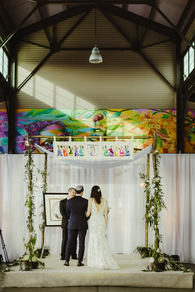 Bride and groom beneath chuppah - Eastern Market wedding recap from Detroit calligrapher Leah E. Moss Designs with photos by Jill DeVries Photography #detroitwedding #moderncalligraphy #custominvitation