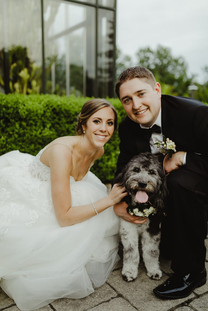 Bride and groom with dog - Elegant Planterra Conservatory wedding. Highlights from Leah E. Moss Designs. Photos by Jill DeVries Photography. #michiganwedding #greenhousewedding #elegantwedding