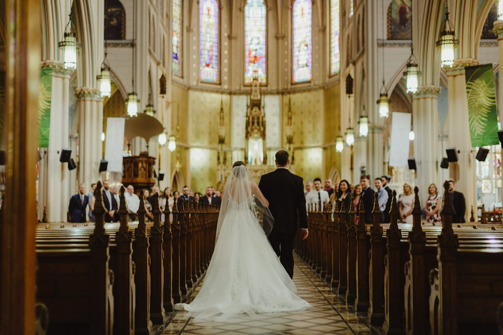 Father and bride walking down the aisle at church - Elegant Planterra Conservatory wedding. Highlights from Leah E. Moss Designs. Photos by Jill DeVries Photography. #michiganwedding #greenhousewedding #elegantwedding