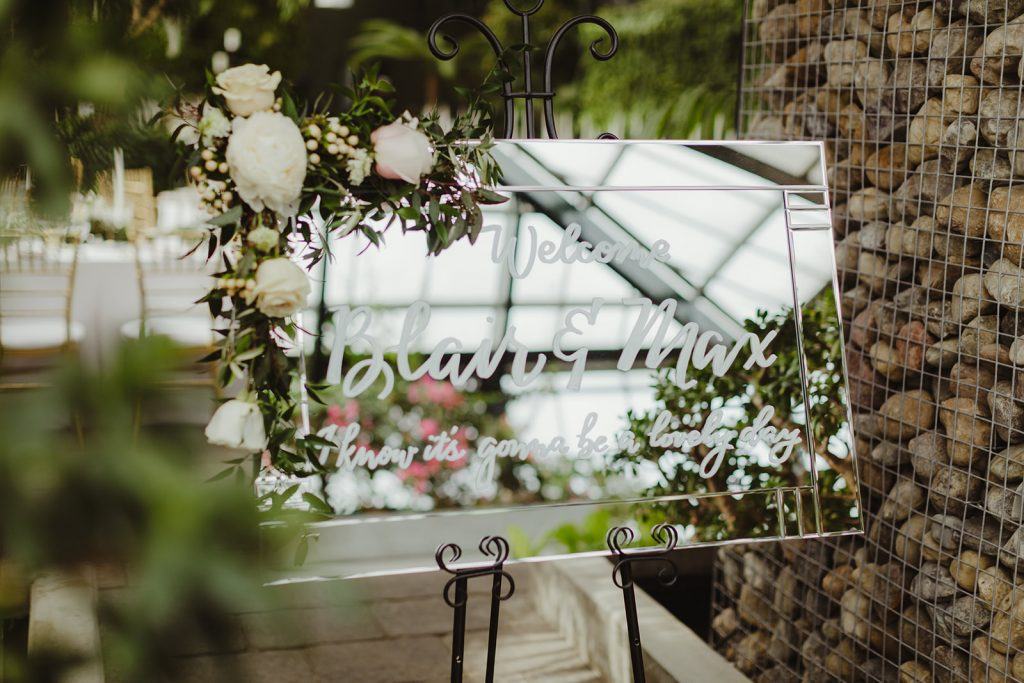 Welcome sign on a mirror - Elegant Planterra Conservatory wedding. Highlights from Leah E. Moss Designs. Photos by Jill DeVries Photography. #michiganwedding #greenhousewedding #elegantwedding