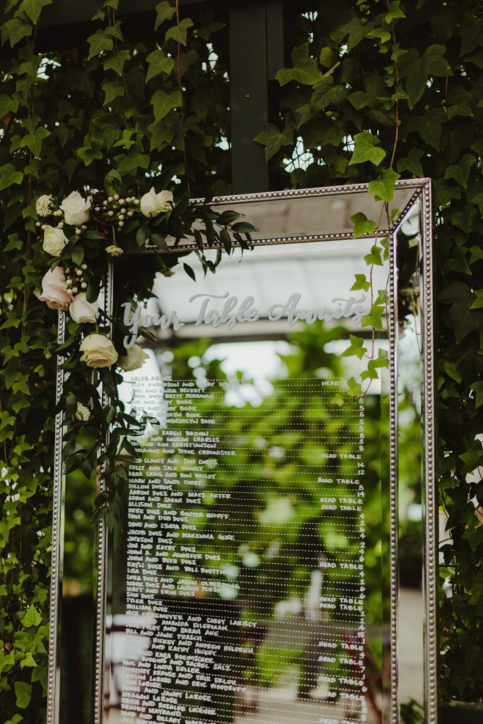 Seating chart on a mirror detail - Elegant Planterra Conservatory wedding. Highlights from Leah E. Moss Designs. Photos by Jill DeVries Photography. #michiganwedding #greenhousewedding #elegantwedding