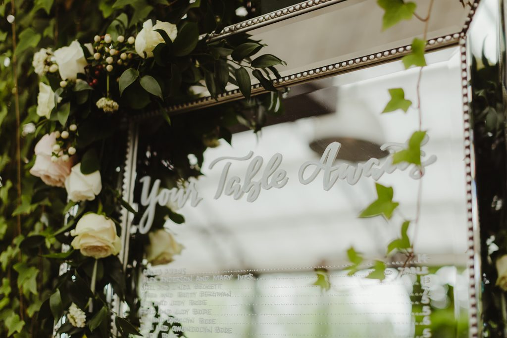 Seating chart on a mirror heading with Your Table Awaits - Elegant Planterra Conservatory wedding. Highlights from Leah E. Moss Designs. Photos by Jill DeVries Photography. #michiganwedding #greenhousewedding #elegantwedding