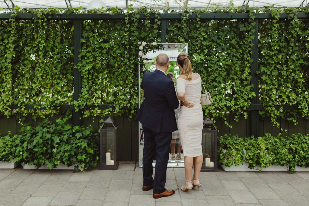 Couple viewing seating chart - Elegant Planterra Conservatory wedding. Highlights from Leah E. Moss Designs. Photos by Jill DeVries Photography. #michiganwedding #greenhousewedding #elegantwedding