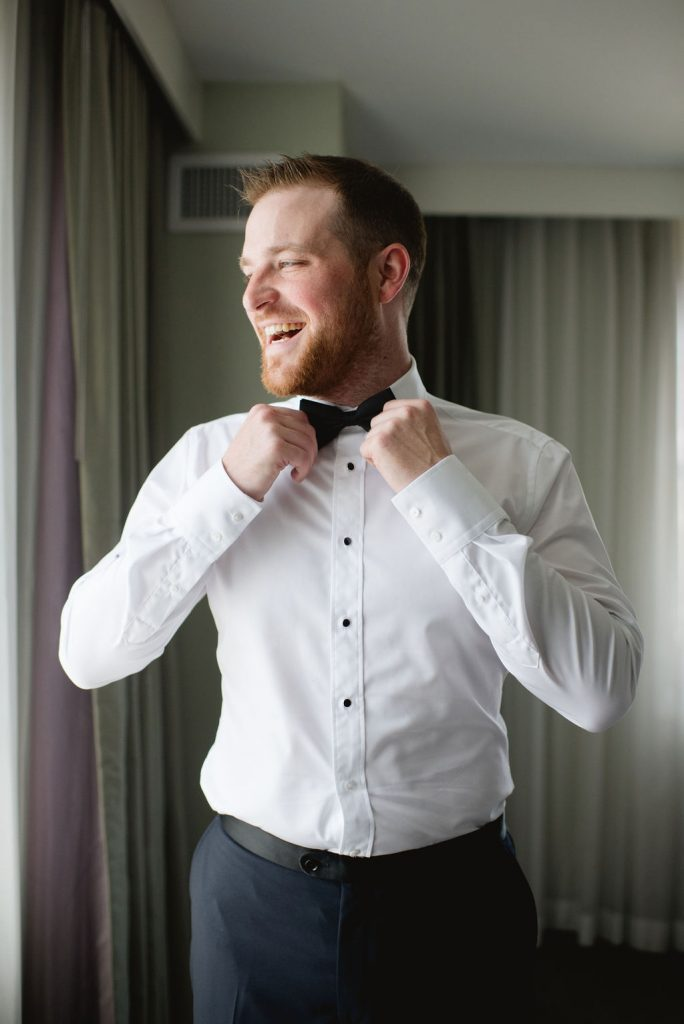Groom getting ready and tying bow tie - Classic and Neutral Wedding at the Garden Theater in Detroit, Michigan - Recap by wedding invitations designer Leah E. Moss Designs with photos by Niki Marie Photography