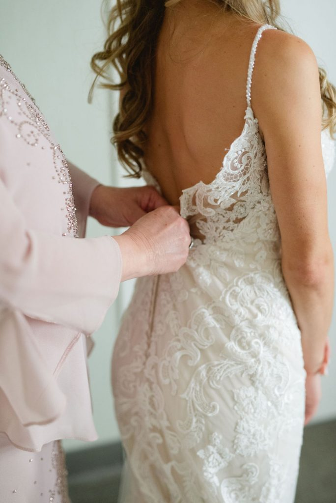 Mom buttoning up back of lace wedding dress - Classic and Neutral Wedding at the Garden Theater in Detroit, Michigan - Recap by wedding invitations designer Leah E. Moss Designs with photos by Niki Marie Photography