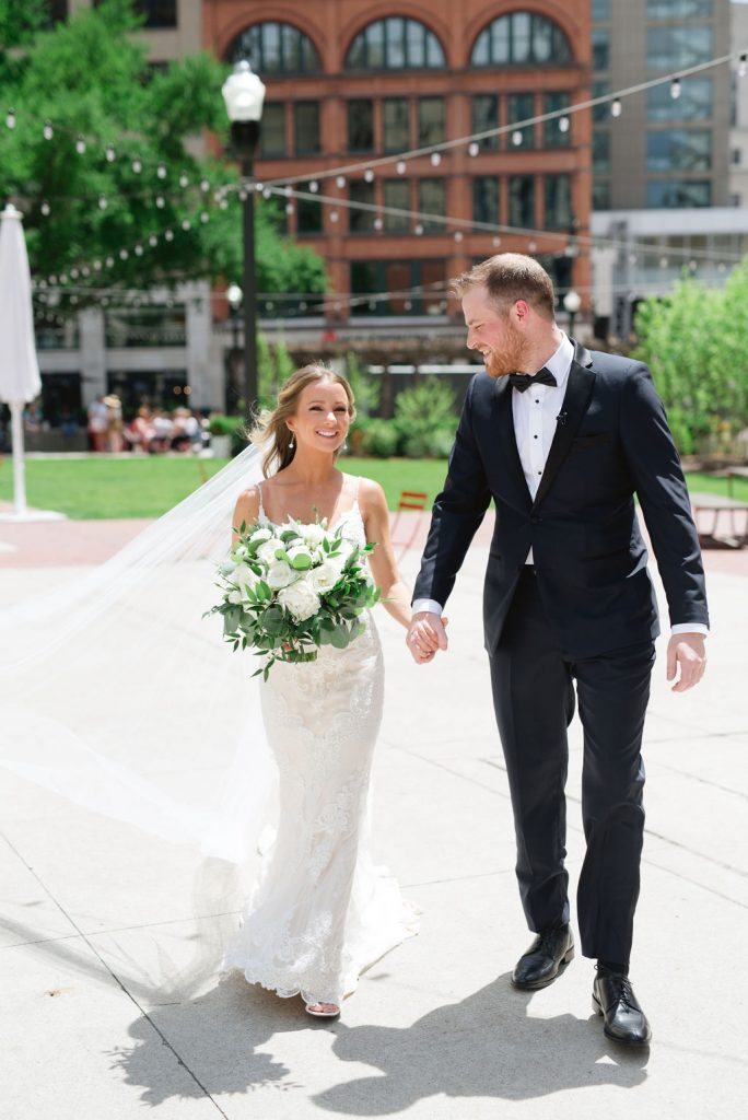Bride and groom holding hands in Detroit park - Classic and Neutral Wedding at the Garden Theater in Detroit, Michigan - Recap by wedding invitations designer Leah E. Moss Designs with photos by Niki Marie Photography