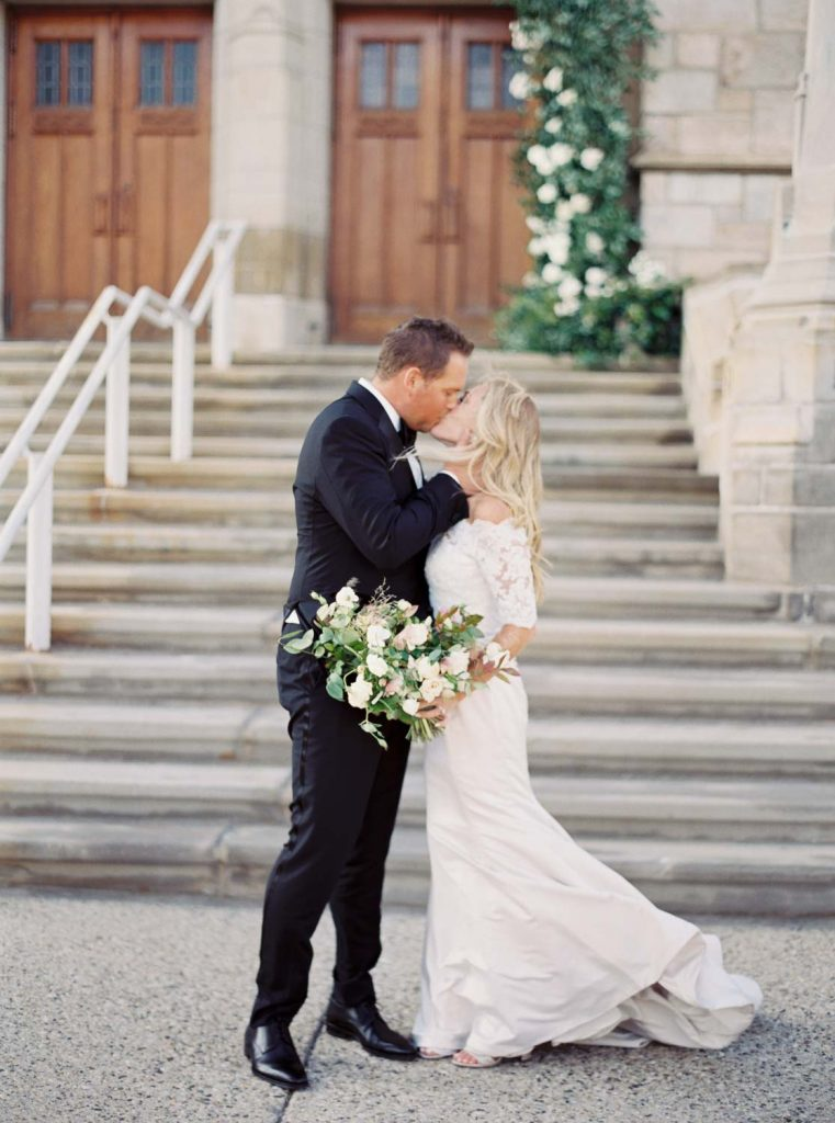 Couple kissing outside church - Traditional Detroit Athletic Club wedding - blog by Leah E. Moss Designs - photography by Blaine Siesser