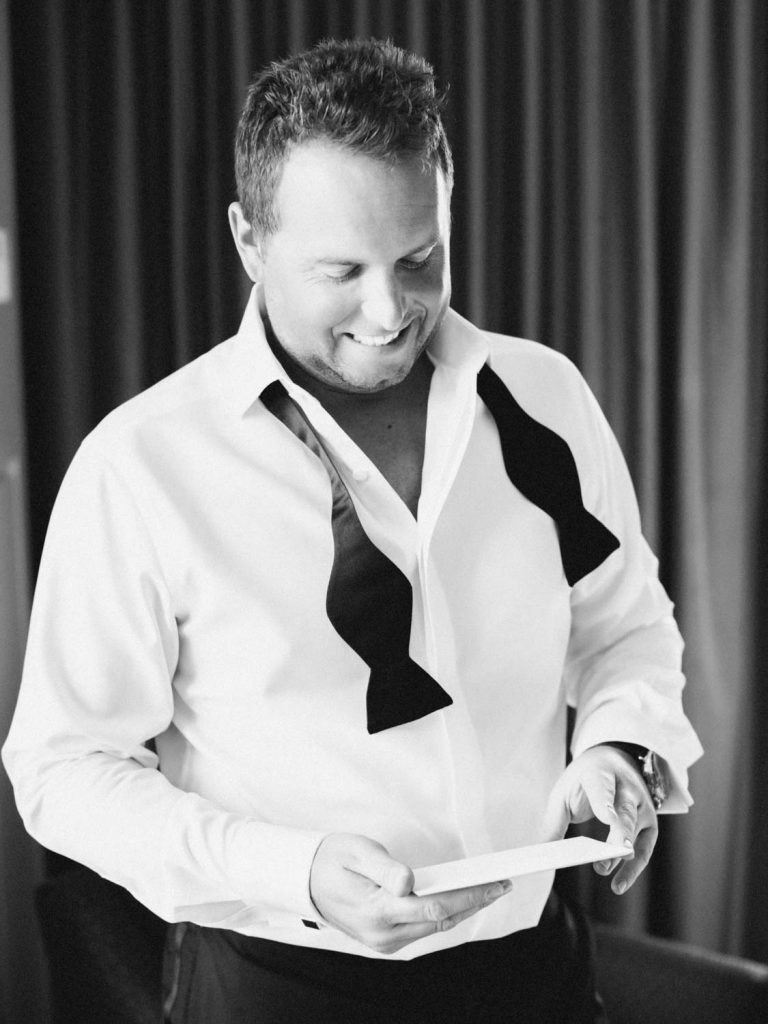 Groom in bow tie reading his wedding card - Traditional Detroit Athletic Club wedding - blog by Leah E. Moss Designs - photography by Blaine Siesser