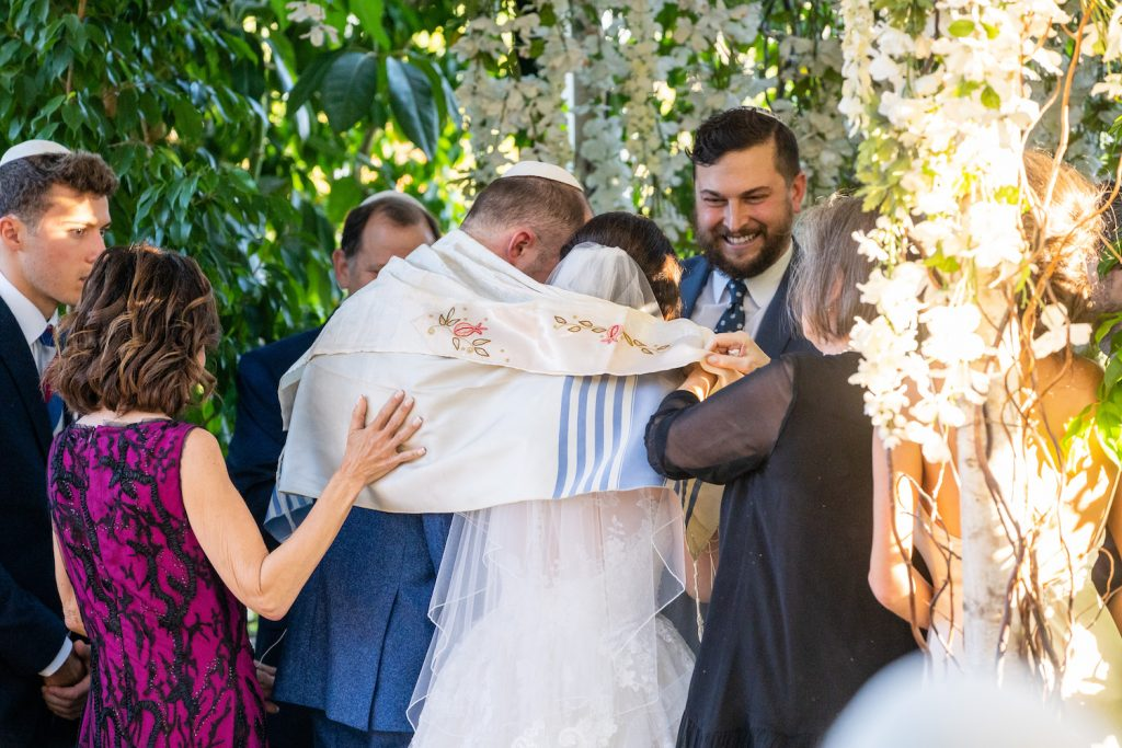 Couple wrapped in Jewish prayer shawl during ceremony - Greenery-filled Planterra wedding - Leah E. Moss Designs