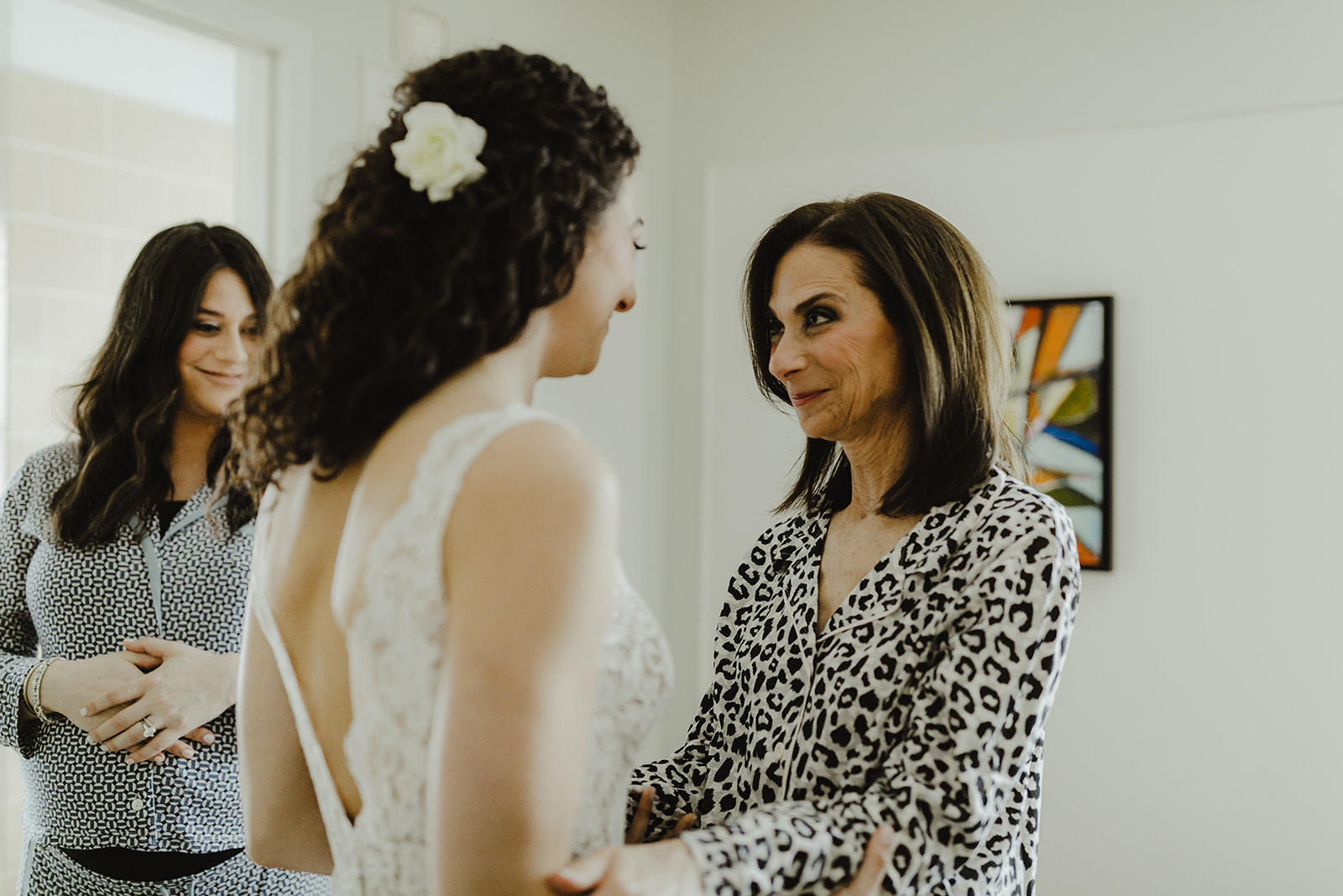 Mother of the bride in leopard pjs and bride's sister look on at the bride's finished look with pride, portrait by Jill DeVries Photography - How mom can help with wedding planning - Leah E. Moss Designs