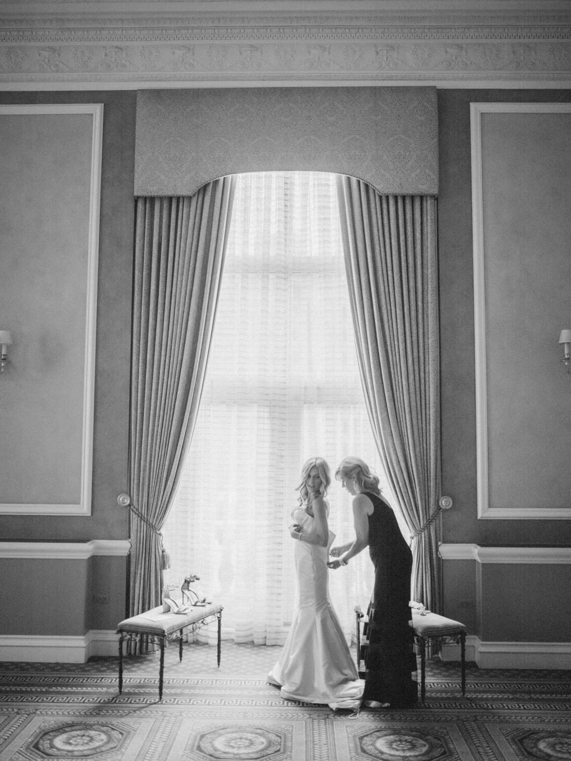 Mom helping bride with dress in front of large window, dramatic black and white portrait by Blaine Siesser - How mom can help with wedding planning - Leah E. Moss Designs