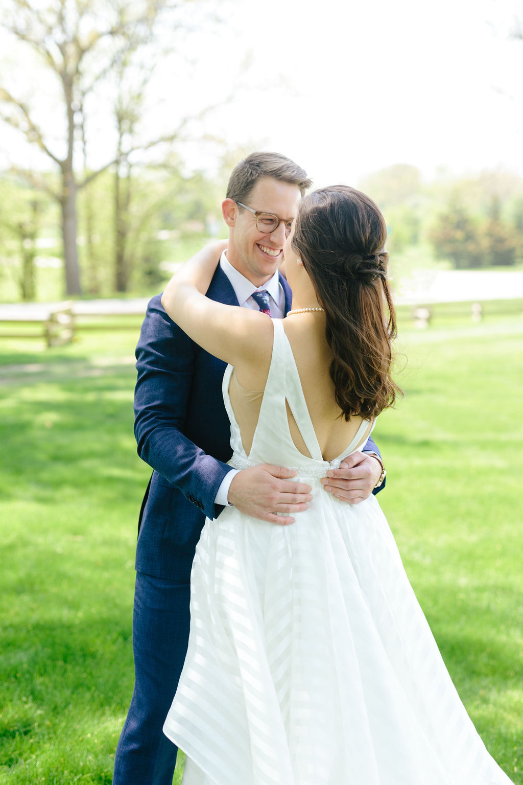 Groom smiling at their first look when he sees his bride - Preppy spring wedding at Zingerman's Cornman Farms - Leah E. Moss Designs - photo by Katie Grace Photography