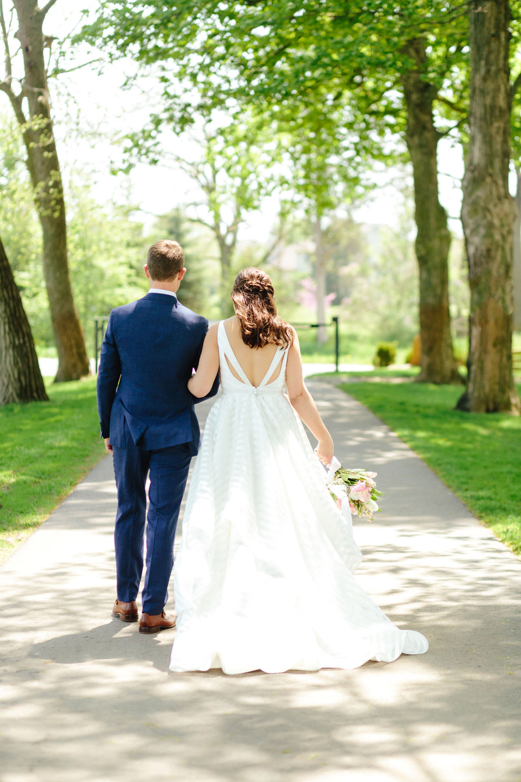 Bride and groom walking - wedding portrait under a canopy of trees - Preppy spring wedding at Zingerman's Cornman Farms - Leah E. Moss Designs - photo by Katie Grace Photography