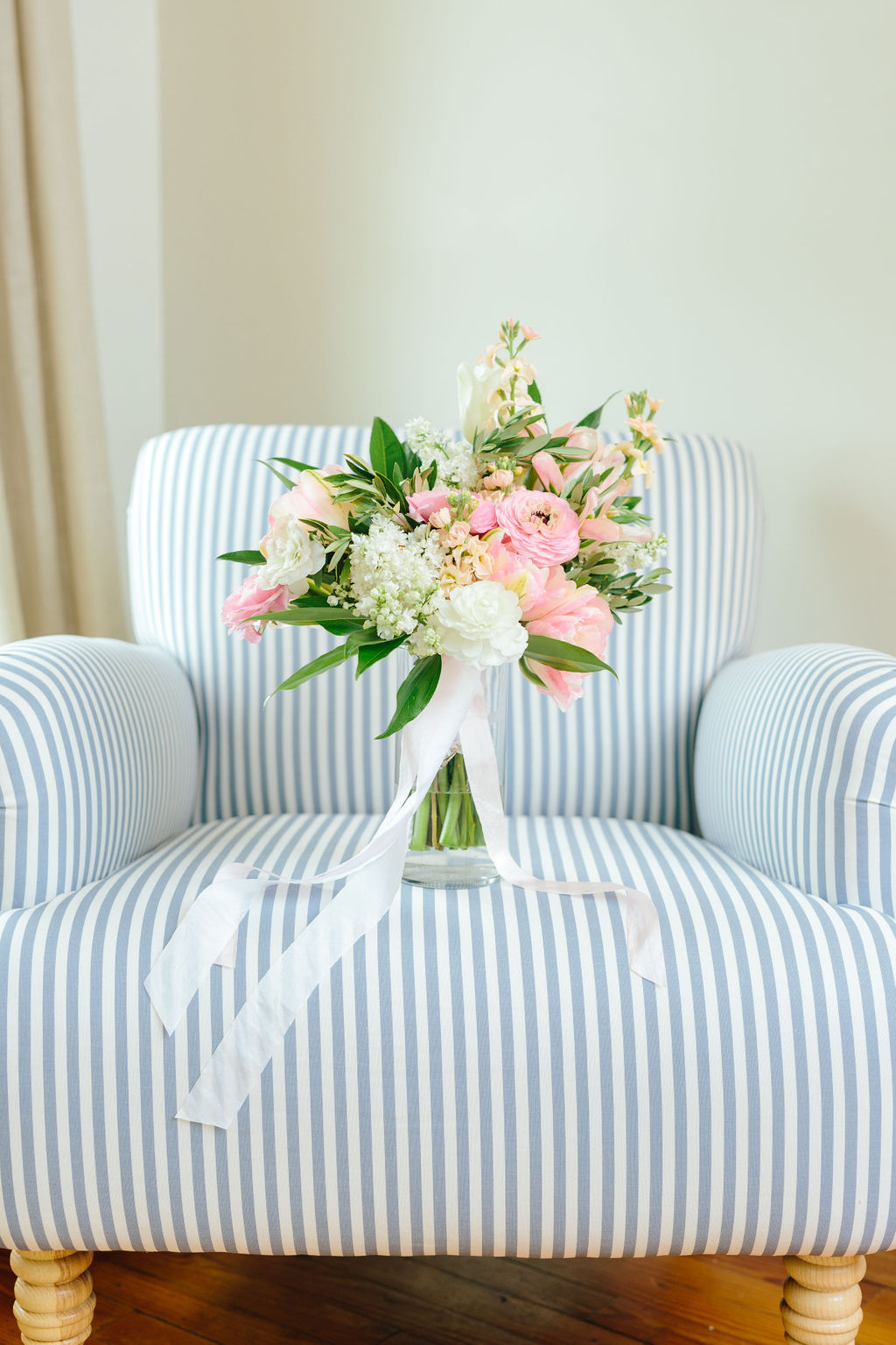 Bouquet with ranunculus and ribbon on striped chair - Preppy spring wedding at Zingerman's Cornman Farms - Leah E. Moss Designs - photo by Katie Grace Photography