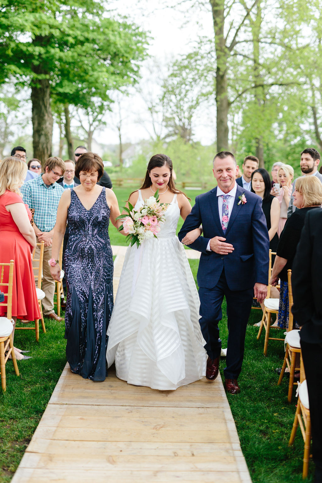 Bride walking down the aisle with her parents - Preppy spring wedding at Zingerman's Cornman Farms - Leah E. Moss Designs - photo by Katie Grace Photography