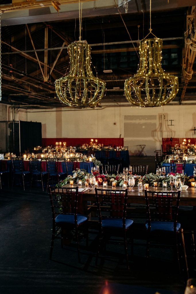 Fairy lights chandelier, burgundy floral garland, navy chiavari chairs, jewel tones, How to use your wedding color palette in a different season - Leah E. Moss Designs - photo: Casey Brodley Photography