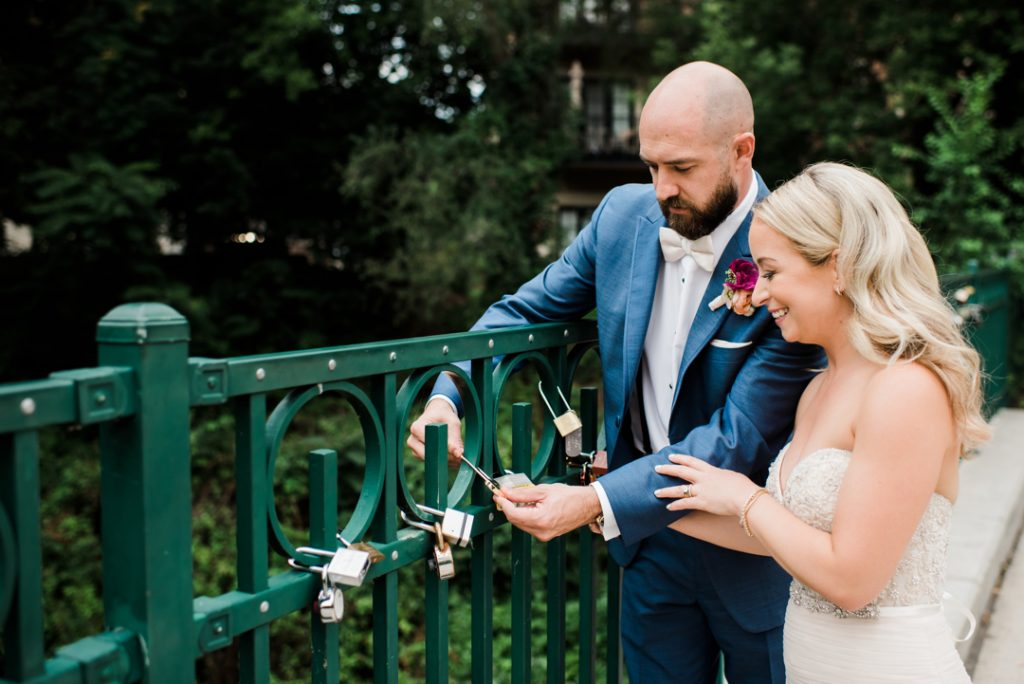 Placing lock on love lock bridge, traditional love lock, love lock bridge in Rochester, Michigan - Royal Park Hotel wedding - Leah E. Moss Designs; photo by Brittany Emerson Photography