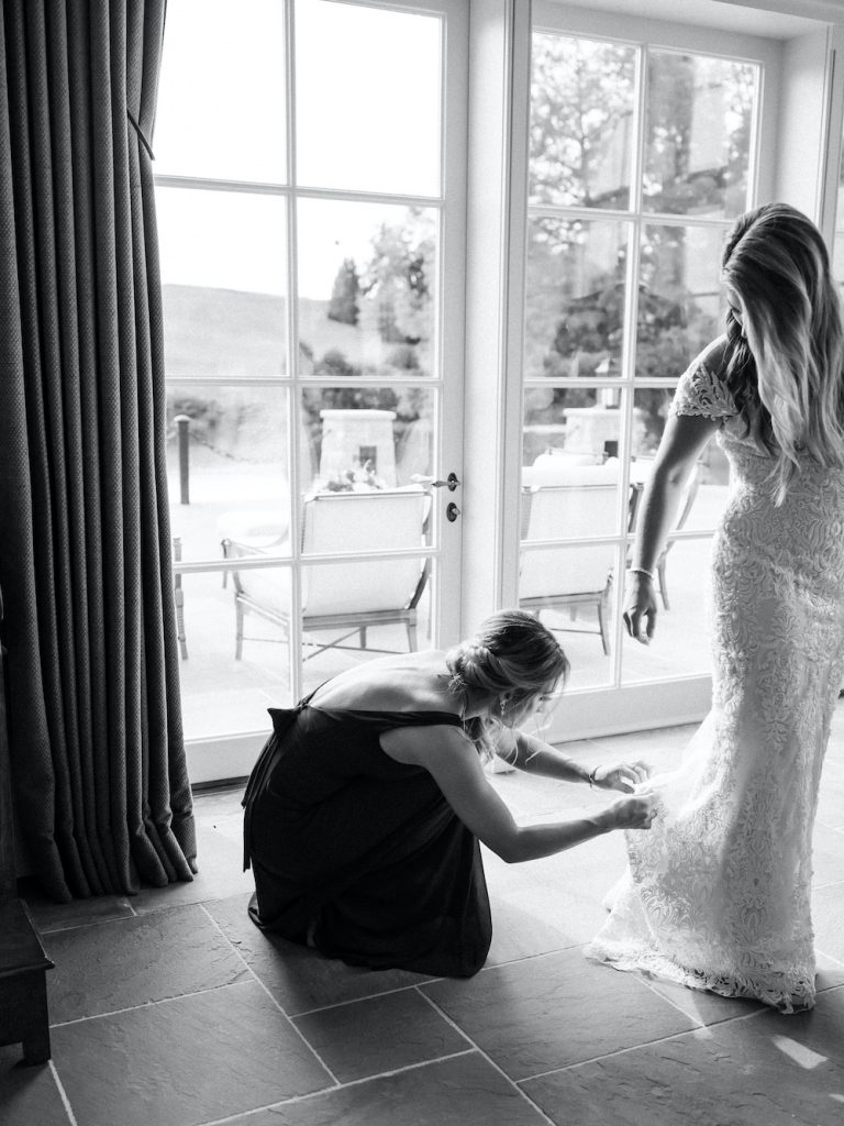 Bridesmaid adjusting wedding gown - Intimate wedding at home in Ann Arbor, Michigan - Leah E. Moss Designs - Photo by Blaine Siesser