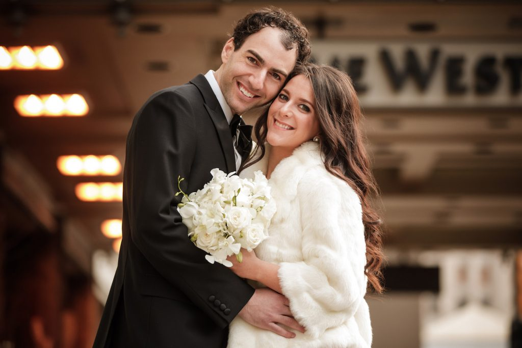 Bride and groom winter wedding portrait in a white fur - An Elegant Book Cadillac Wedding in black, gold, pink, and white - Leah E. Moss Designs