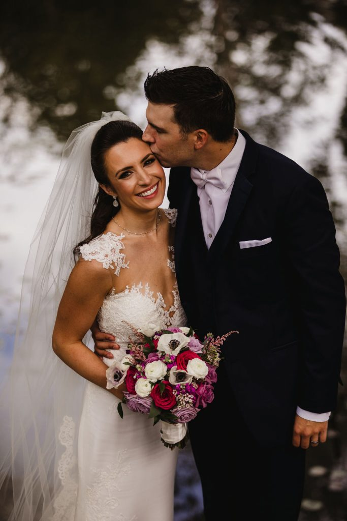 Bride and groom portrait with bouquet - Purple and pink florals for wedding at Oakland Hills Country Club in Bloomfield Hills, Michigan - Leah E. Moss Designs