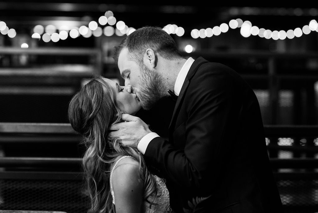 Couple kisses during reception in black and white photo - Classic and Neutral Wedding at the Garden Theater in Detroit, Michigan - Recap by wedding invitations designer Leah E. Moss Designs with photos by Niki Marie Photography