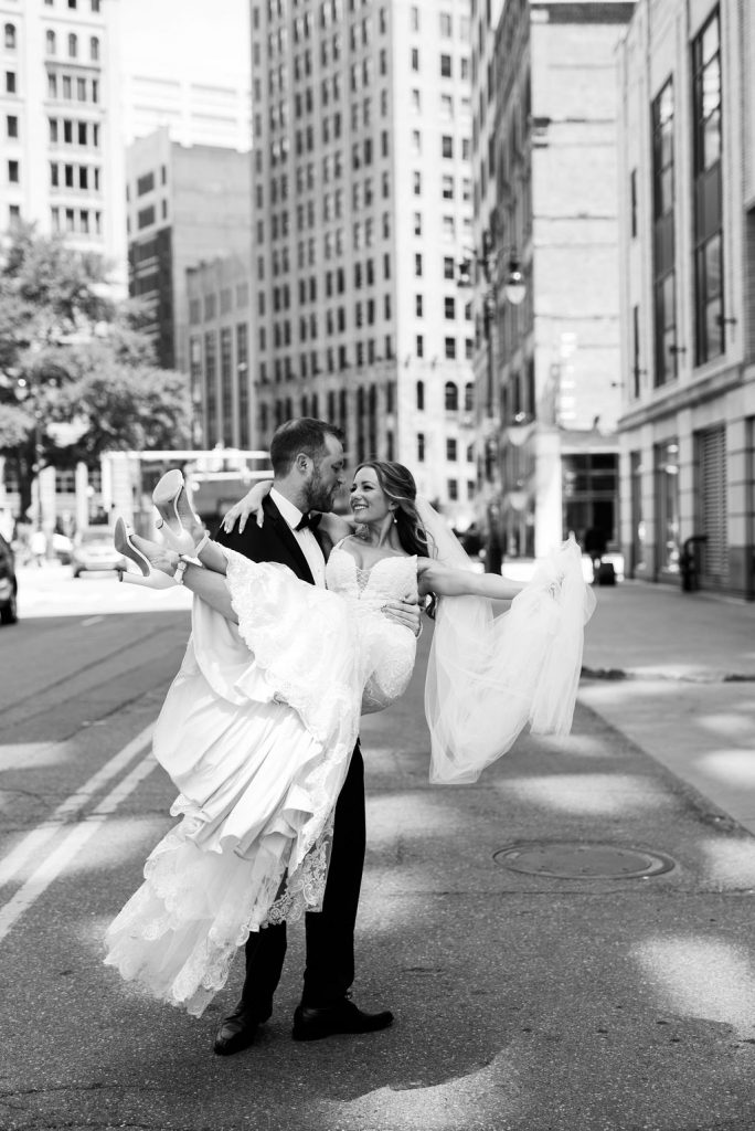 Groom carrying bride in downtown street - Classic and Neutral Wedding at the Garden Theater in Detroit, Michigan - Recap by wedding invitations designer Leah E. Moss Designs with photos by Niki Marie Photography