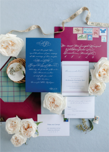 Vintage postage on burgundy envelope with cobalt blue invitation and plaid liner - Invitation embellishments to take your stationery over the top - Leah E. Moss Designs