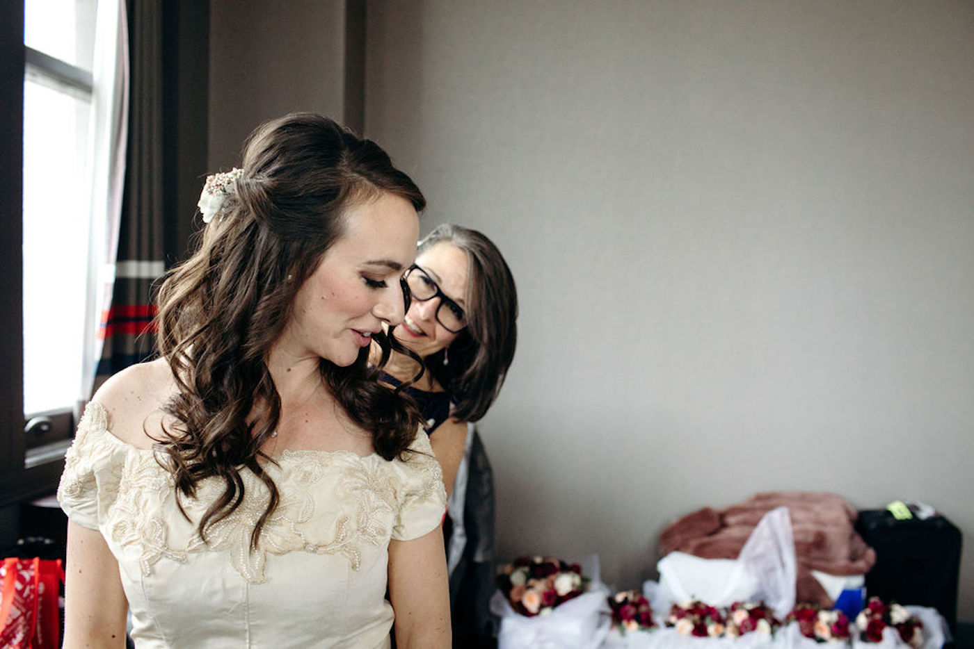 Bride and mom, buttoning her wedding dress - How mom can help with wedding planning - Leah E. Moss Designs, photo by Casey Brodley