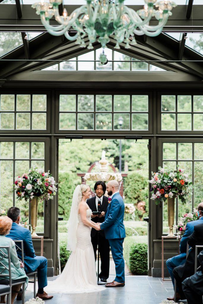 Wedding ceremony in conservatory, unique wedding locations, ceremony location, wedding ceremony florals, bright wedding flowers - Royal Park Hotel wedding - Leah E. Moss Designs; photo by Brittany Emerson Photography