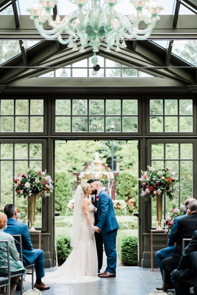 Couple's first kiss in the conservatory - Royal Park Hotel wedding - Leah E. Moss Designs; photo by Brittany Emerson Photography